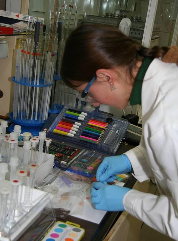 Zdjęcie - naukowiec testująca artykuły piśmiennicze oraz farbki do malowania