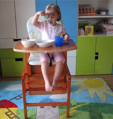 Zdjęcie - dziecko jedzące śniadanie na krześle ze stolikiem