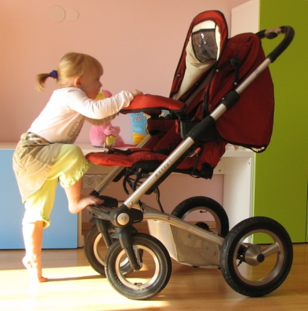 Zdjęcie - dziecko wdrapujące się na wózek spacerowy
